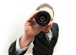 レンズで覗く男性