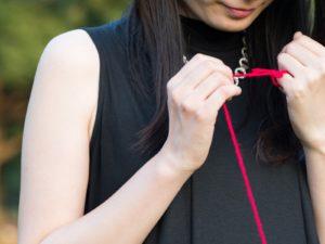 赤い糸を小指に巻き付けている女性
