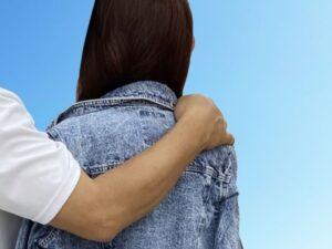 女性の肩に手を回す男性