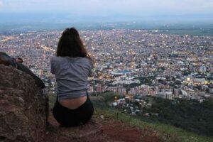 山の上から街を見下ろす女性