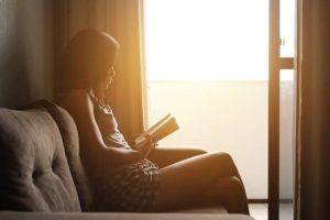 夕陽が差し込む部屋でソファに座って本を読む女性